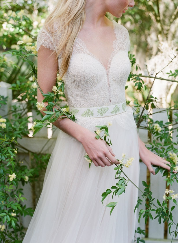 "Divine Atelier's ""Celia"" gown from Gown  Boutique of Charleston. Rock crystal and rose  gold ring from Roberto Coin. Green and fern ribbon used as a sash from style team's  collection"