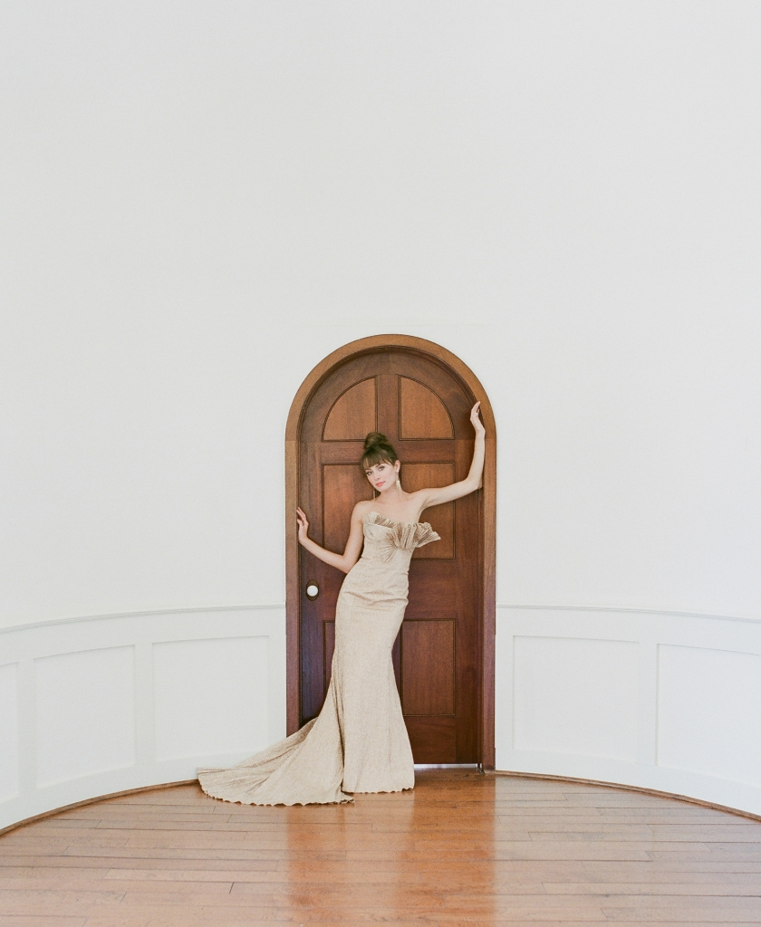"""Carol Hannah's  """"Narcisseae"""" rose gold  metallic trumpet gown with pleated train and  bust from Southern  Protocol Bridal.  <i>Photograph Corbin Gurkin</i>"""