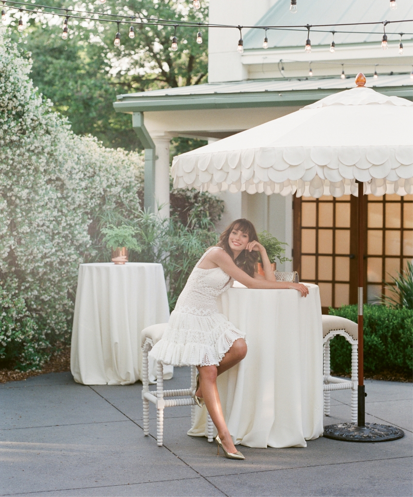 Enchanting by Mon Cherie's Style 117195  A-line lace shortie from Palmetto Bridal  Boutique.  Scallop-canopied  umbrella by Anne  Girault of Boutique Tents; stand from  Snyder Events. Stools from Ooh! Events. Linens and tables from EventWorks. Plants from Roadside Blooms.  <i>Photograph Corbin Gurkin</i>