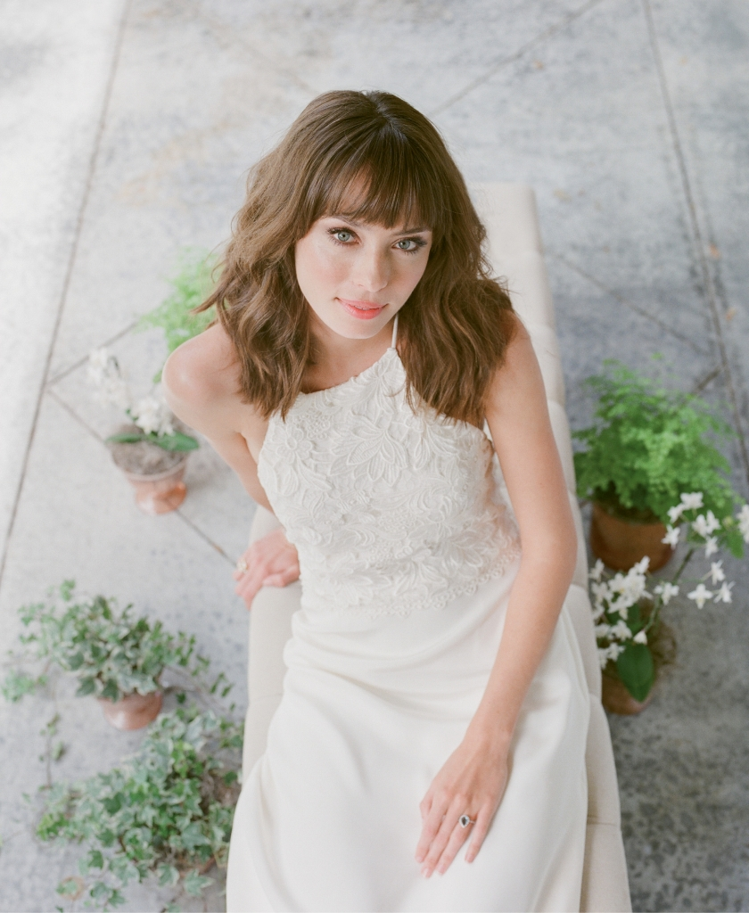 """Katherine McDonald's """"Kipling"""" Guipure  lace and silk crepe  gown from Kate  McDonald Bridal  (also available through  Lovely Bride). Royal Jewelry's blue topaz  and gold ring from Diamonds Direct.  Bench from Snyder Events. Plants from Roadside Blooms.   <i>Photograph Corbin Gurkin</i>"""