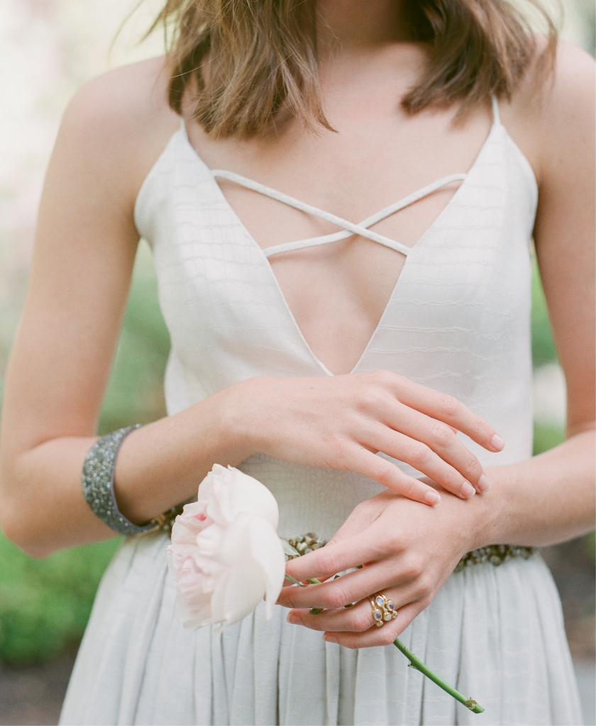 """Danielle Mason Hosker's  """"Audrey"""" gown with  vintage beading and crisscross detail from Mason Hosker. Mazza's moonstone, diamond, and gold stacked ring from Croghan's Jewel Box. ZZan's gunmetal crystal cuff from Berlin's for Women. Peony from Roadside Blooms.   <i>Photograph Corbin Gurkin</i>"""
