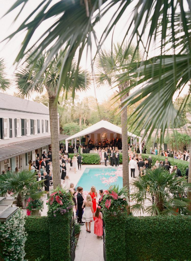 "At first, the plan was to cap the pool with a dance floor. In the end, Gathering Events made the pool a focal point by filling it with blooms. ""It was one of my favorite aspects of the wedding,"" says Cate."