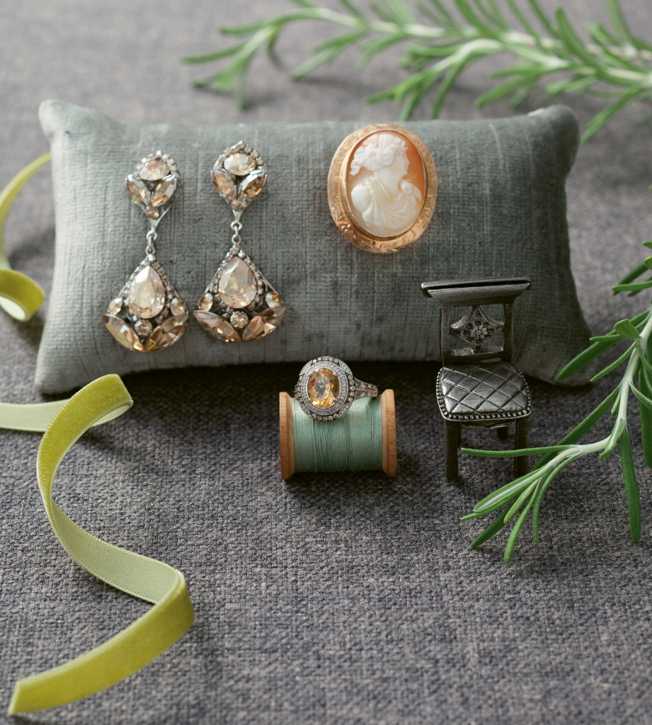 """(clockwise from left) Sara Gabriel's """"Jasmine"""" earrings from Maddison Row. Antique cameo brooch from Croghan's Jewel Box. Sterling silver, citrine, and diamond ring from REEDS Jewelers. Ribbon from May Arts. Fabric from GDC Home. Pillow from Croghan's Jewel Box.  Photography by Gayle Brooker"""