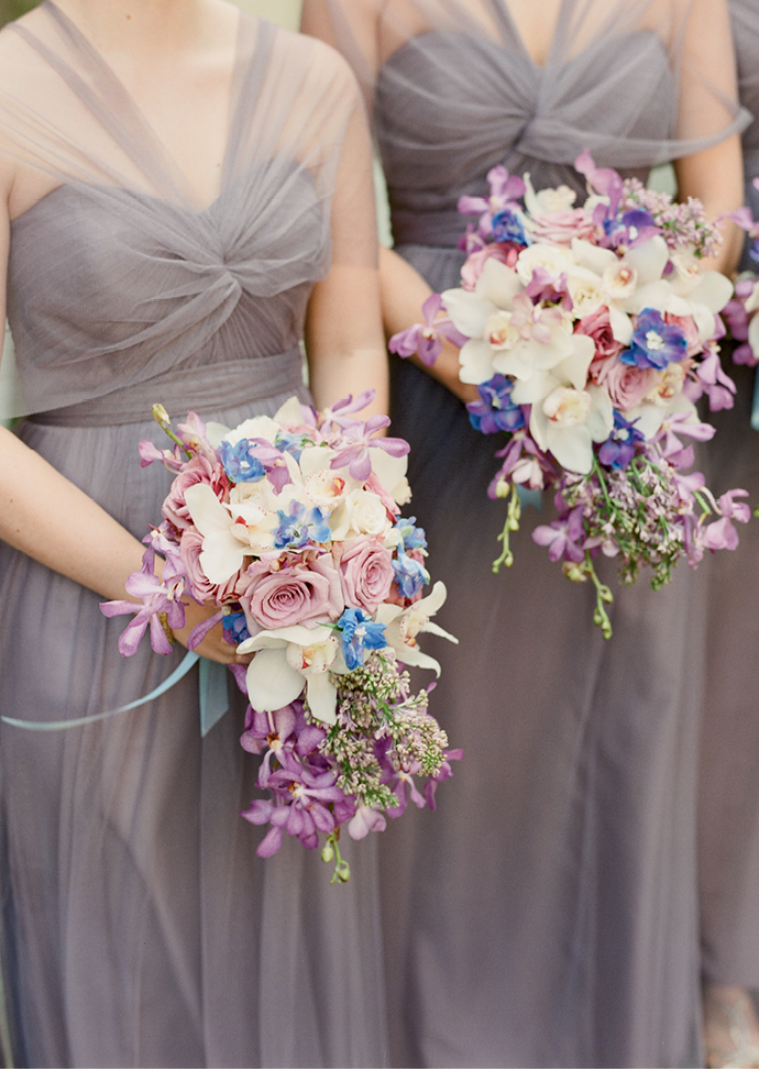 """""""We've seen a shift from tightly packed  handheld florals to loose, more organic arrays,"""" Tara  explains of the cascading bridesmaid bouquets. (Photo by Corbin Gurkin)"""