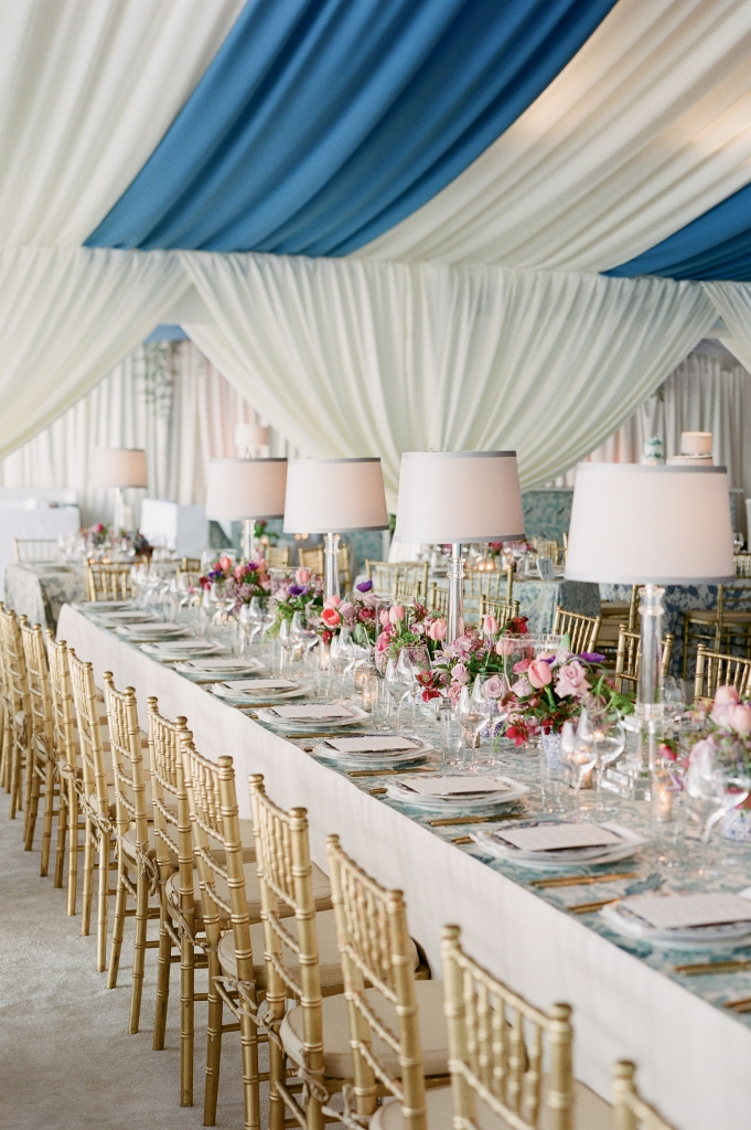 """When the couple selected French Blue as their central color, Tara wondered, """"Everyone loves a blue-and white-wedding, but how can we make it stand out?"""" Mix-and-match fabrics did the trick. Tables were dressed in a mélange of custom-made linens in blue-hued florals, patterns that offset the bold ceiling draping. The final touch? Sheer white curtains around the perimeters.  (Photo by Corbin Gurkin)"""