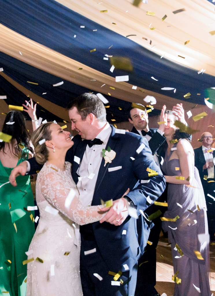 """""""Skip and I had a rule that we would take breaks every so often to hold hands and savor the details together,"""" Laura explains. Exhibit A: this stolen moment just as the confetti cannon exploded. (Photo by Corbin Gurkin)"""