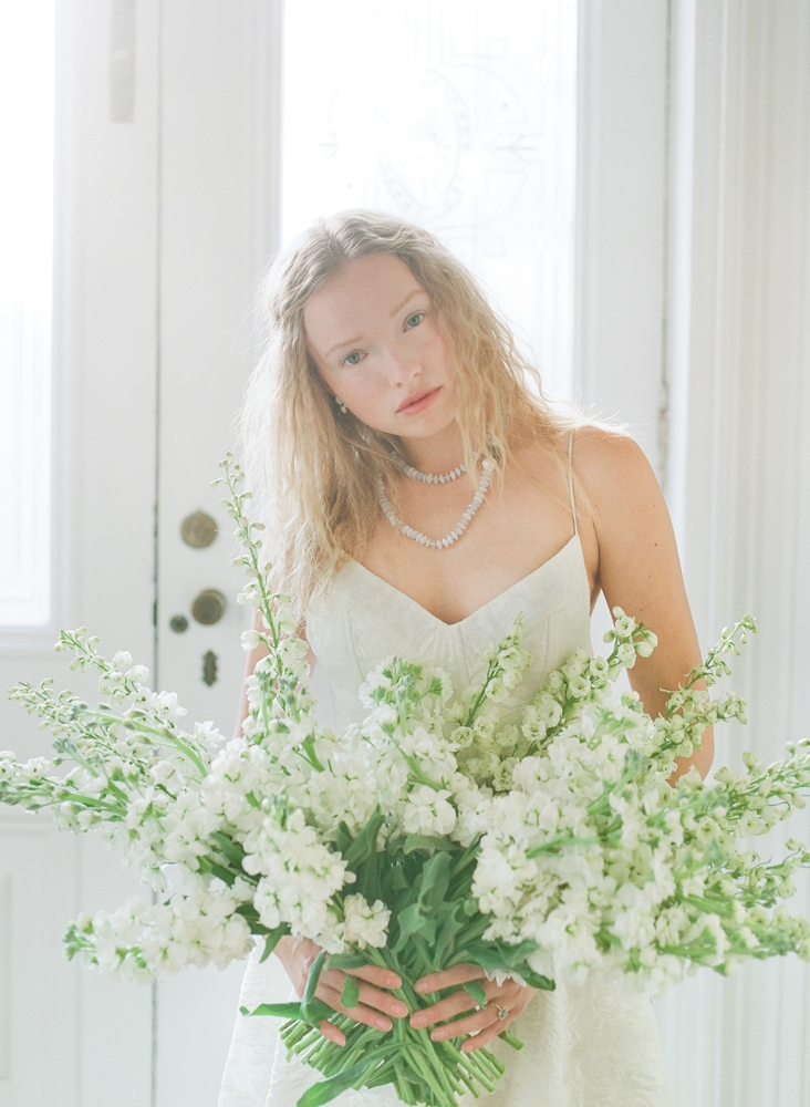 """Lela Rose's """"The Desert"""" floral fil coupé gown from Maddison Row. Swarovski crystal and milkstone earrings from Gown Boutique of Charleston. Colibri Collections chalcedony necklace from RTW. Hybrid delphinium and stock flowers from Tiger Lily Weddings. <i>Photograph by Corbin Gurkin</i>"""