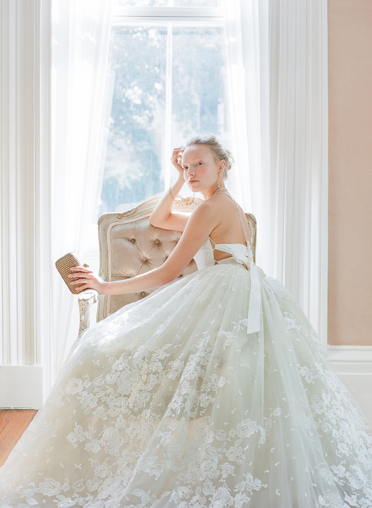 """Emily Kotarski's """"The Bowieite  Separates"""" lace-up taffeta corset bodice from Emily Kotarski Bridal Studio. Casablanca Bridal's """"Aspen"""" A-line overskirt from Palmetto Bridal Boutique, worn atop Emily Kotarski's """"The Bowieite Separates"""" silk tulle skirt from Emily Kotarski Bridal Studio. Tatum Triple Ring Collection gold and pale pink drop earrings from Peyton William. Leather and pearl lariat necklace from Out of Hand. Freida Rothman's gold bracelet from Gwynn's of Mount Pleasant (shown on issue's cover). Izi Creations' morganite and diamond ring from Diamonds Direct (shown on issue's cover). Santi's bronze studded clutch from Berlin's for Women. <i>Photograph by Corbin Gurkin</i>"""
