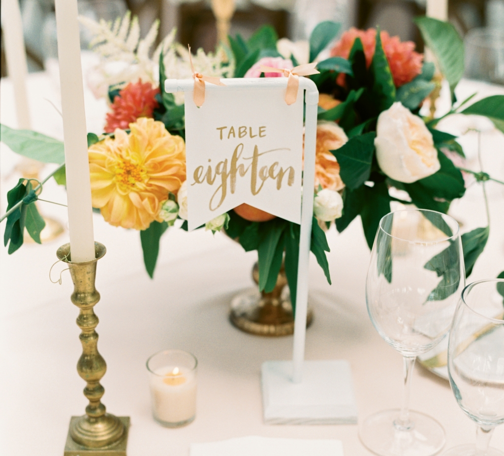 Sweet, simple details like these tables marked with pennants, peaches tucked into floral arrangements, and homey brass candlesticks can make a standout statement.