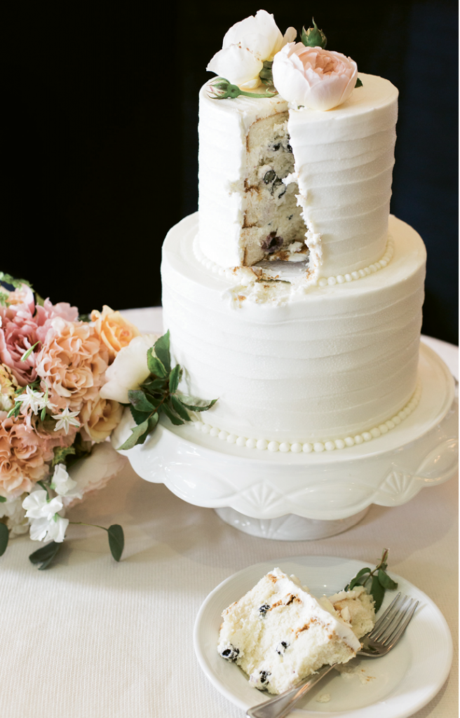 """The bride craved an organic diet during her pregnancy, so Ashley Bakery skipped colored icing and relied on blueberries to deliver the """"It's a boy!"""" message with the gender reveal wedding cake."""