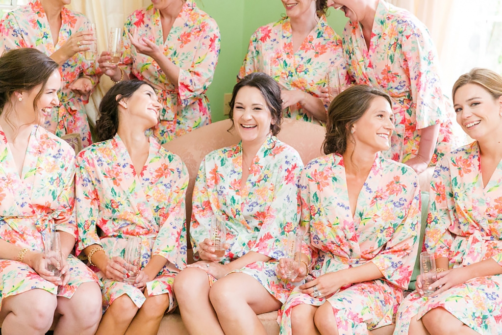 """Made of breezy cotton, the bridesmaids' robes—a gift from the bride—were as practical as they were pretty on the sultry wedding day. In a triumph of kismet coordination, they also matched bold floral tablecloths that stole the show during cocktail hour. """"My mom and I found the linens first, so perhaps subconsciously I was thinking about them while searching for robes,"""" says Andra."""