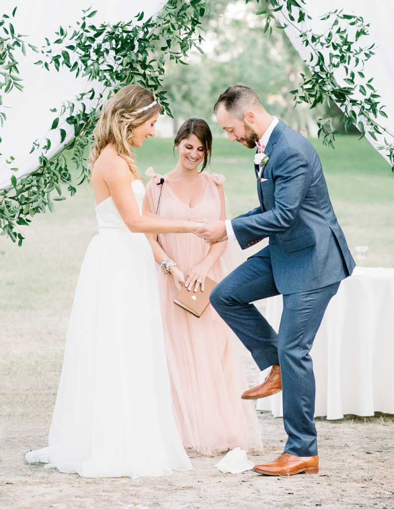 """""""Our amazing  officiant made the ceremony so personable, unique, and fitting for us,"""" says Dani. As a nod to her Jewish roots, Andrew sealed their vows by breaking a glass.  <i>Image Aaron & Jillian Photography</i>"""