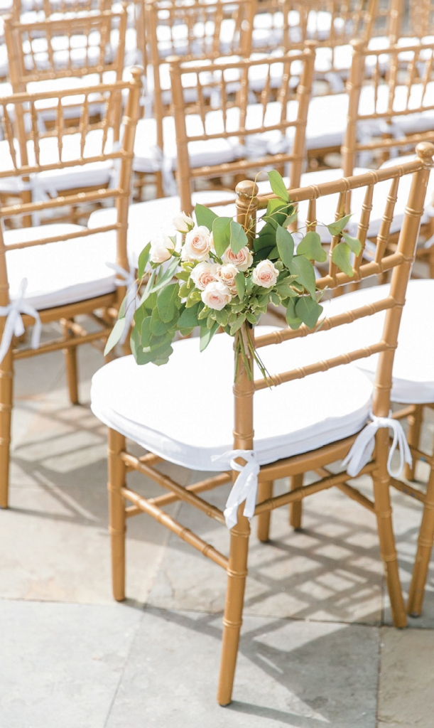 TIP: Opt for classic chiavari chairs. The gilded version of the bamboo chairs never go out of style. Pair them with snow-white cushions and table linens to temper the elegance for a summery vibe.  Image by Dana Cubbage Weddings
