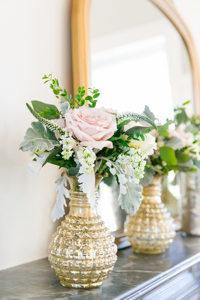 TIP: Pair shiny gold with shimmering crystal and mercury glass. Toasting flutes rimmed with gold, a glass cake stand with a hammered gold base, brass candelabras, and a collection of golden mercury glass-style vases echoed the subtle sparkle without overpowering the setting.  Image by Dana Cubbage Weddings