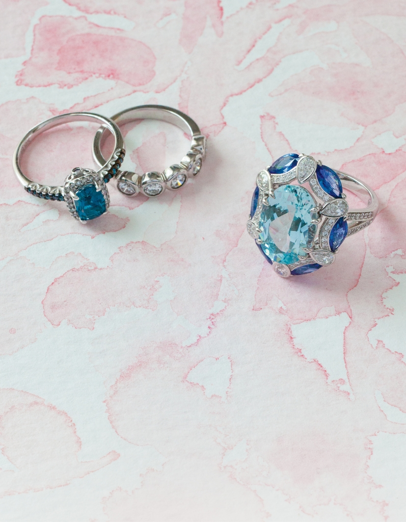 (from left) 10K white gold ring  with London blue topaz center, white diamond halo, and blue accent diamonds (.17 total cts.) from REEDS Jewelers, $625. Forevermark's 18K white gold band with bezel-set diamonds (.68 total cts.) from Paulo Geiss Jewelers, $3,895. 18K white gold ring with 5.85 ct. aquamarine center, accent diamonds (.92 total cts.), and sapphires (2.35 total cts.) from Roberto Coin, $16,500. Artwork by Natalie Taylor Humphrey