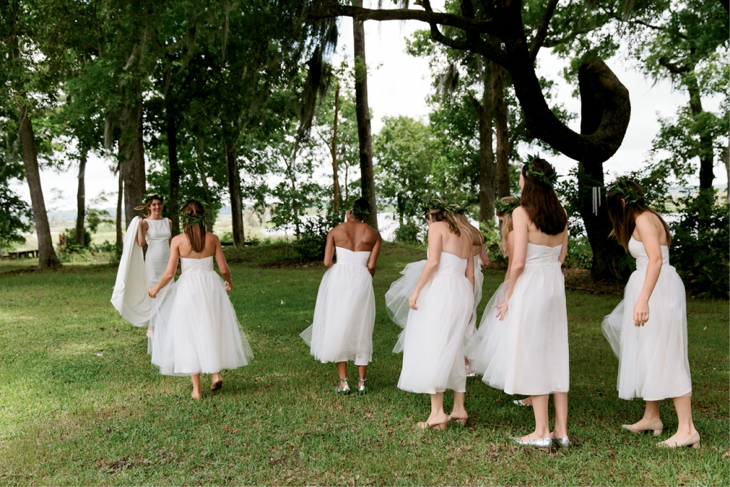 """Bridesmaids wore tea-length white tulle dresses from Alexandra Grecco. """"With their flower crowns, they looked like little nymphs!"""" says the bride.  <i>Photograph by Olivia Rae James</i>"""