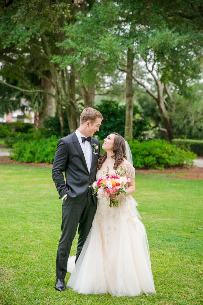 Bride's gown by Monique Lhuillier, available in Charleston through Maddison Row. Hair and makeup by Paper Dolls. Groom's attire by Hugo Boss. Florals by Branch Design Studio. Image by Dana Cubbage Weddings at Lowndes Grove Plantation.