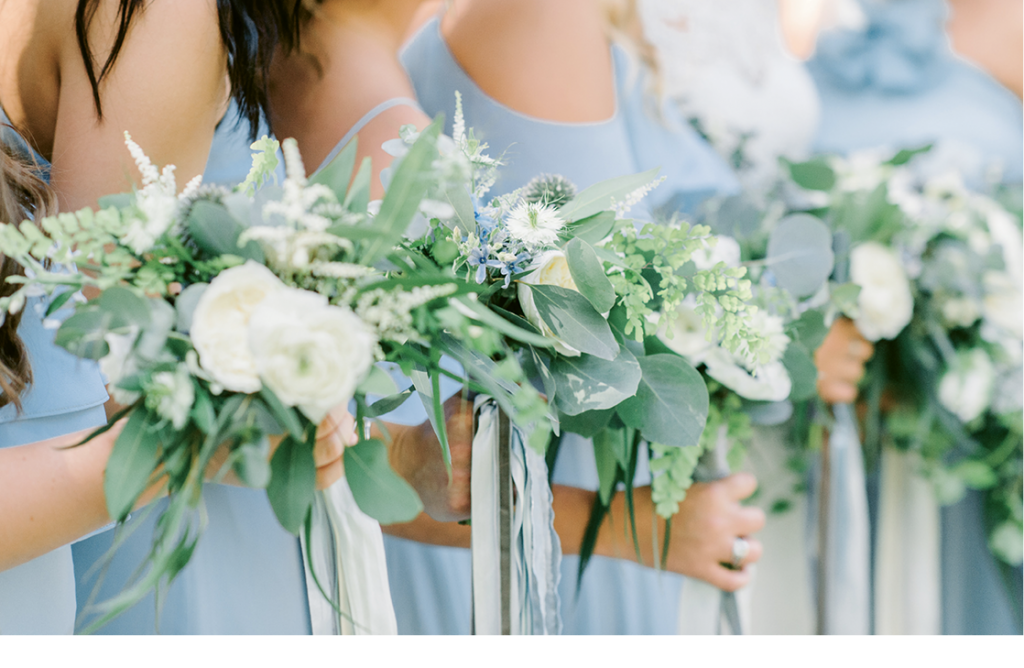 SYG Designs made bouquets dominated by greenery and dotted with blue and white blooms. Trailing ribbons that danced in the breezes added to the florals' airy style.