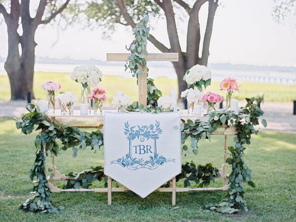 Wedding crest by Arabella June. Altar banner by Blossoms Events. Wedding and floral design by A Charleston Bride. Image by Ryan Ray Photography at Lowndes Grove Plantation.