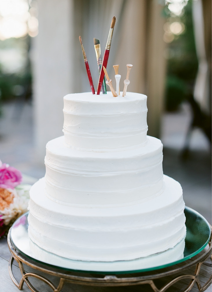 "As a nod to the couple's professions, paintbrushes and golf tees topped the dessert. ""We cleaned them thoroughly before sticking them in the cake!"" laughs Teil. (Image by Natalie Franke Photography)"