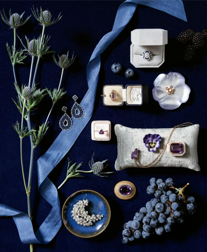 """(clockwise from left) Rebeka Hakimi Jewelry's white gold, sapphire, and diamond earrings  from Diamonds Direct. Gold and amethyst ring from Gold Creations. White gold diamond and sapphire ring from Kiawah Fine Jewelry. Alexis Bittar's """"Jolie Fleur"""" resin and pearl pin from Out of Hand. Gold, amethyst, pearl, and enamel brooch from Croghan's Jewel Box. Gold pansy diamond and enamel pin from Joint Venture Estate Jewelers. Gold and amethyst necklace from Paulo Geiss Jewelers. Gold, amethyst, and pearl brooch from Croghan's Jewel Box. Ben-Amun's crystal brooch from Gwynn's of Mount Pleasant. White gold, garnet, and diamond ring from REEDS Jewelers. Fabric from GDC Home. Pillow from Croghan's Jewel Box. Ring boxes from Croghan's Jewel Box and Victor Barbone. Photograph by Gayle Brooker"""