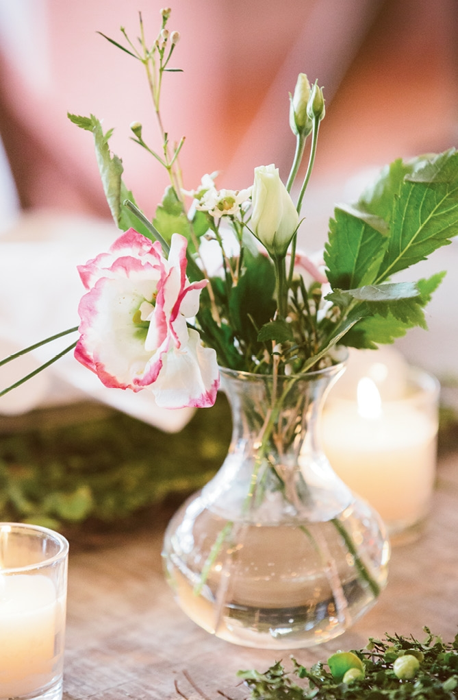 Diminutive vases decorated tabletops so as not to compete with the flower feature wall and hanging arrangements.  <i>Amelia + Dan Photography</i>