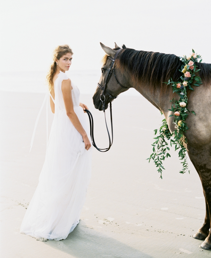 """""""Kendall"""" corseted tulle gown with pearl accents by Emily Kotarski Bridal. Pearl jacket earrings from Southern Protocol Bridal. Carolina Marsh Tacky pony, """"Silky"""", from Seabrook Island Club Equestrian Center. Florals by Out of the Garden. Location: Seabrook Island, Beach Access 6.  Photograph by Perry Vaile"""