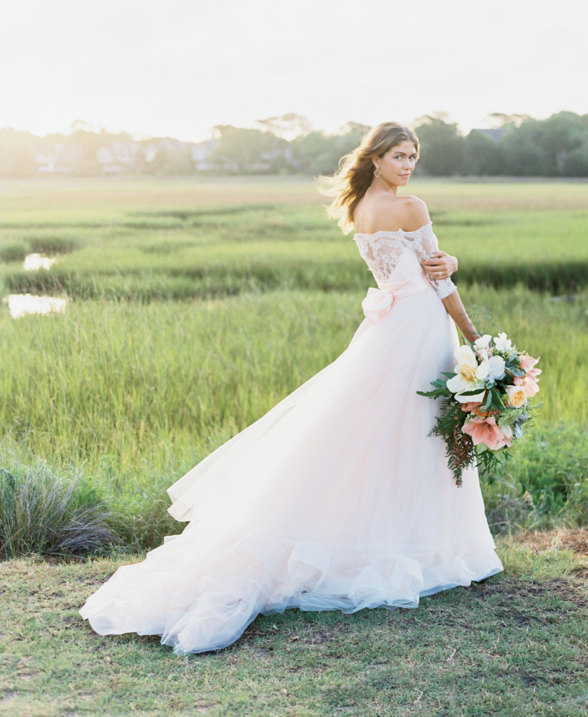Tara Keely's Alençon lace and tulle gown in peach and sherbet from Verità. A Bridal Boutique. Jude Frances's earrings from Croghan's Jewel Box. Morganite and diamond rose gold ring from Gold Creations. Ribbon sash from The Gown Collective. Bouquet by Out of the Garden. Location: Seabrook Island, Seabrook Island Road.  Photograph by Perry Vaile