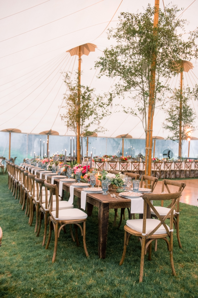 """""""The tent was gorgeous, but very tall,"""" says florist Anne. """"Adding oak branches to the poles made the space more intimate."""" <i>Image by Timwill Photography</i>"""