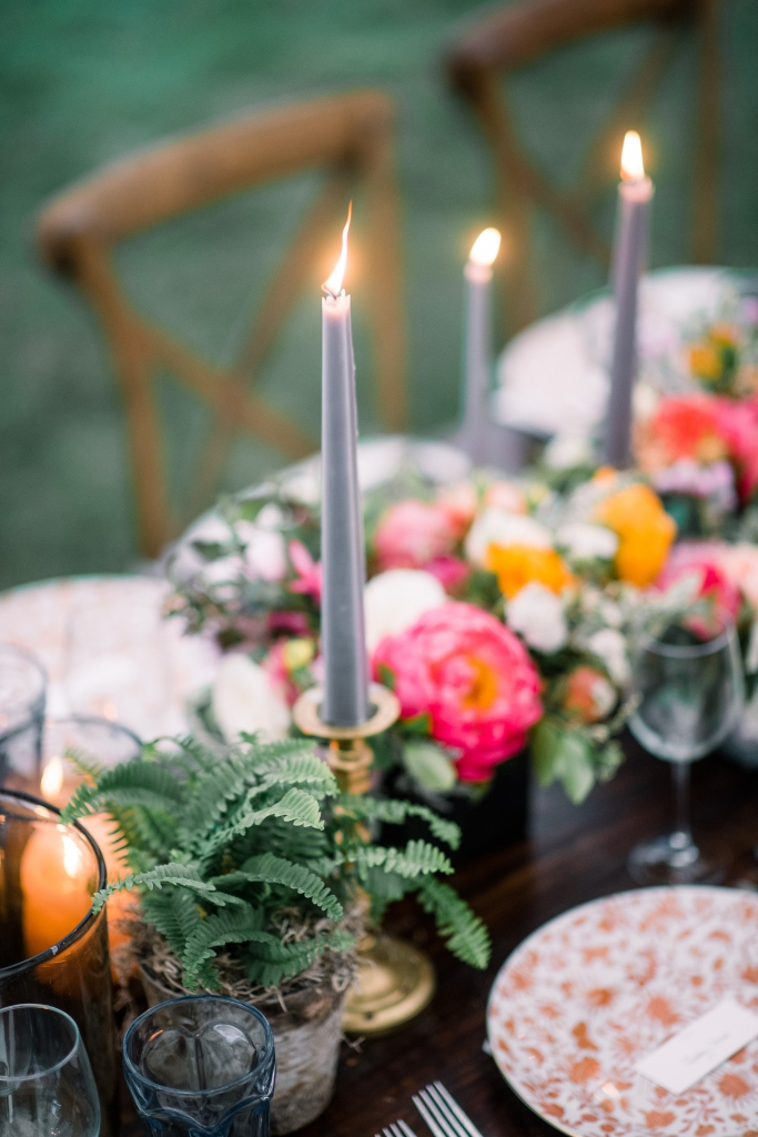 """""""We wanted the tablescape to be cohesive, but not too manicured,"""" says planner Chloe Ewing. The result was an earthy mix of terra cotta, metallics, succulents, glowing votives, and blue taper candles—a nod to Jane's favorite hue. <i>Image by Timwill Photography</i>"""