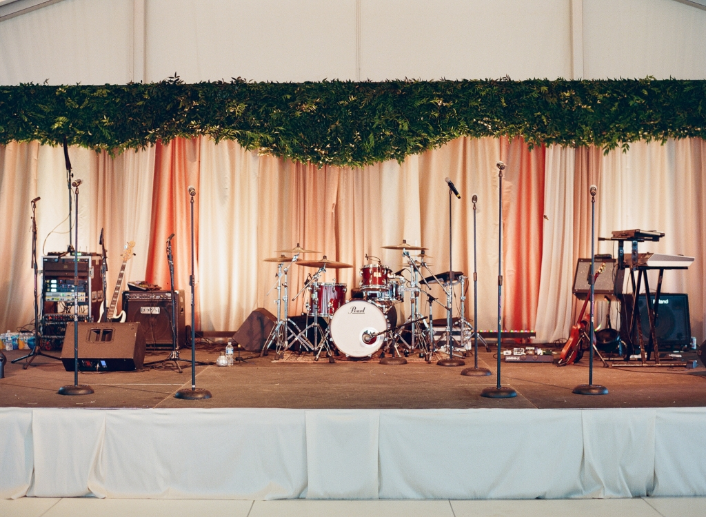 Ombré draping capped with a valance of greens gave the band (and the bride's brother) a stunning stage on which to entertain the crowd. <i>Image by Lucy Cuneo Photography</i>