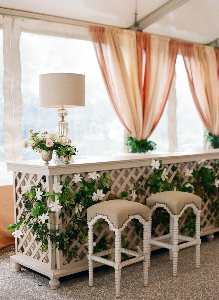 """White clematis crept along the 24-foot trellis-adorned bar. """"Brides don't have to use gobs of  linen throughout their party,"""" says Calder of the organic design. """"Textures like wood, metal, and  painted elements can elevate with ease."""" Lamps and barstools added a homey touch to the area. <i>Image by Lucy Cuneo Photography</i>"""