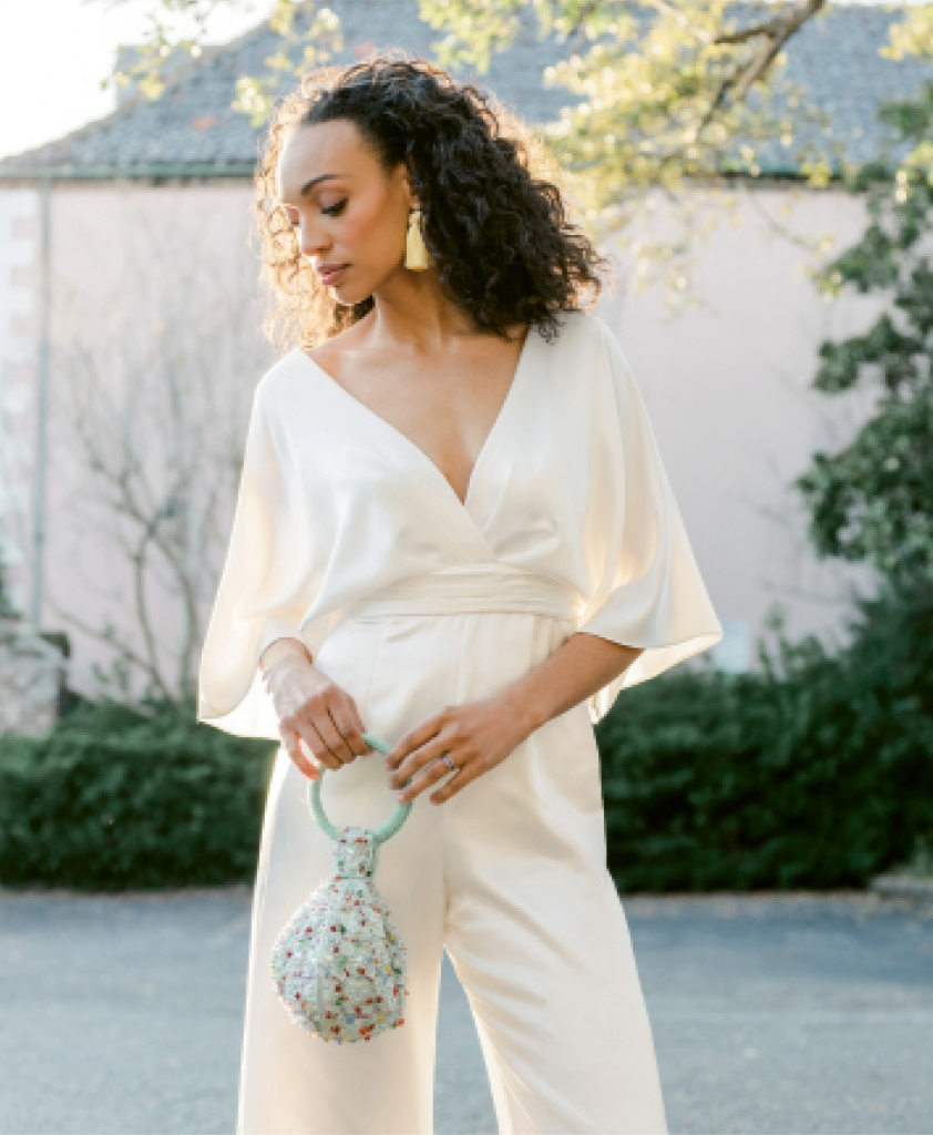 "Theia's ""Simona"" silk kimono-sleeved jumpsuit from Fabulous Frocks. Hart Hagerty's topknot tassel earrings from Hart. Sapphire band and rutile ring, both from Croghan's Jewel Box. David Jeffery's beaded bag from Out of Hand."