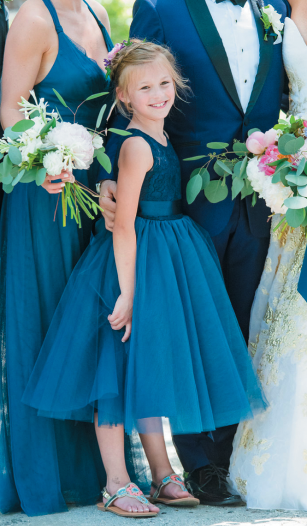 Flower girl Natalie, a niece of the couple, executed her duties perfectly. By portrait time, she let her hair down a little, and slipped into her own comfortable sandals. And by the time the music started? She was in her favorite sundress. Image by Dana Cubbage Weddings