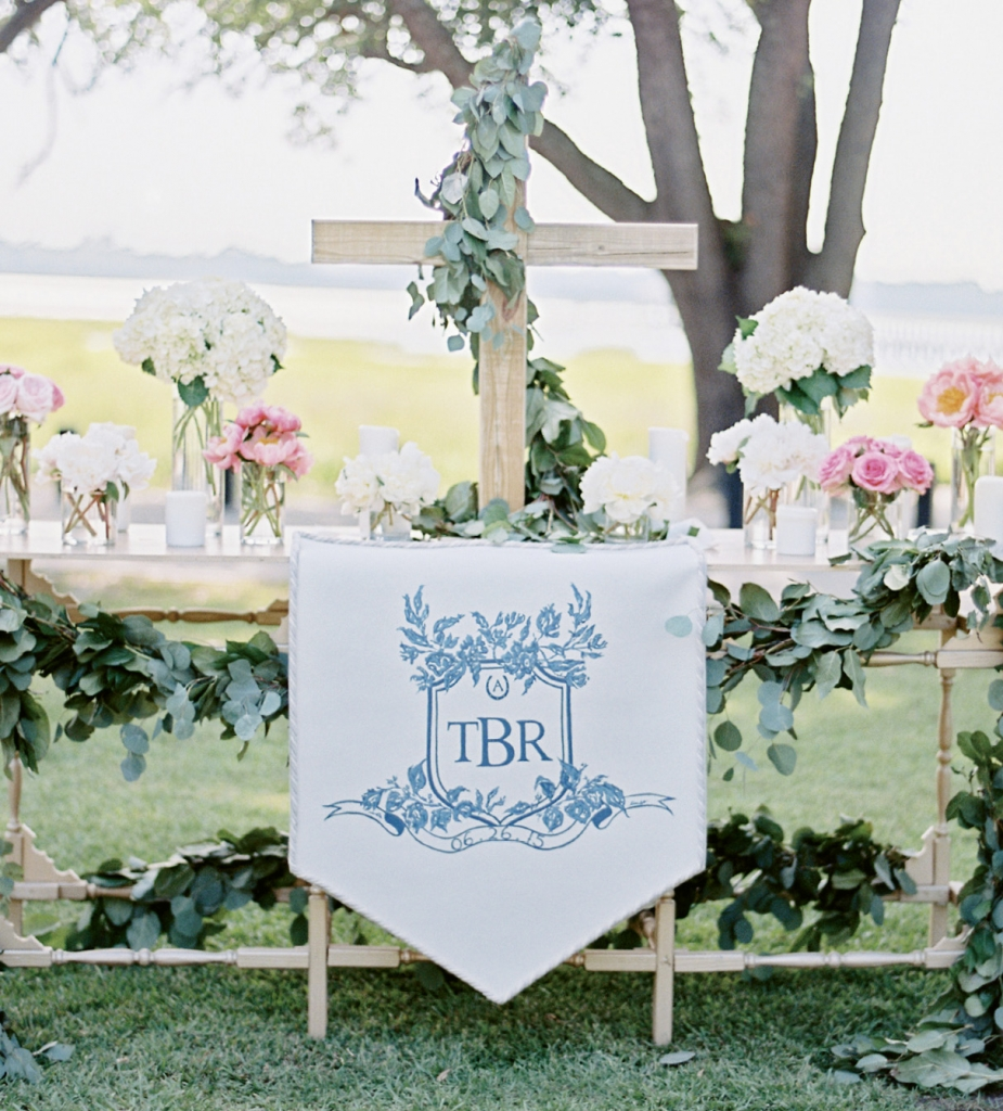 Charleston's Boutique Tents re-interpreted a commissioned crest by Arabella June on this banner that was draped on the ceremony altar. The full-color version of the crest appeared on labels used in the welcome boxes each guest received. Image by Ryan Ray Photography