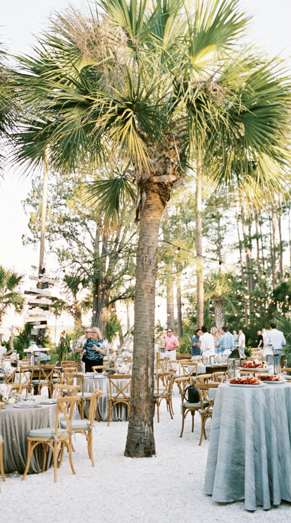 """Café lights, to-the-ground linens, and cushioned X-back chairs elevated the rustic setting. """"Mixing big city touches with South Carolina's natural charm"""" was the aim of Michelle, who lives in Chicago."""