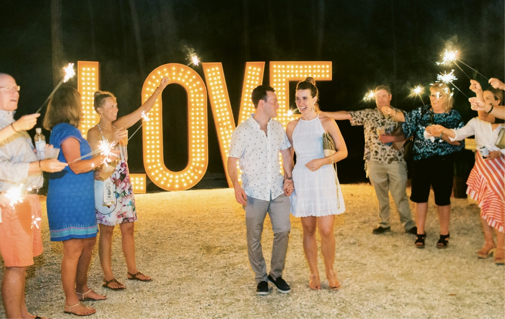 """Because they had to skip sparklers at the reception, the groom's mother surprised the couple with sparks aplenty as they headed out from the welcome party. """"We—Maddy, her mother, Audrey Rohde, and planner Ashley—worked together to create each wedding weekend event unique in its own right and so each one would flow into the other,"""" says Michelle. The crescendo? A charming chapel ceremony and lavish al fresco reception. Visit TheWeddingRow.com for all the Big Day images."""