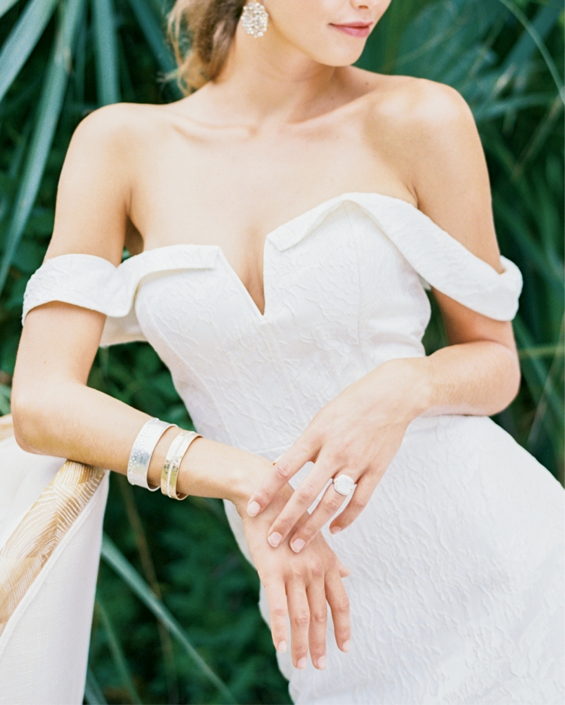 """Rebecca Shoneveld's """"Devon"""" corseted fit-to-flare Spanish jacquard gown from Southern Protocol Bridal. Beaded drop earrings from Copper Penny. Bracelets from Out of Hand. Jude Frances's moonstone and diamond ring from Croghan's  Jewel Box. Chair from Ooh! Events. Location: Seabrook Island Lake House, Pond Trail. Photograph by Perry Vaile"""